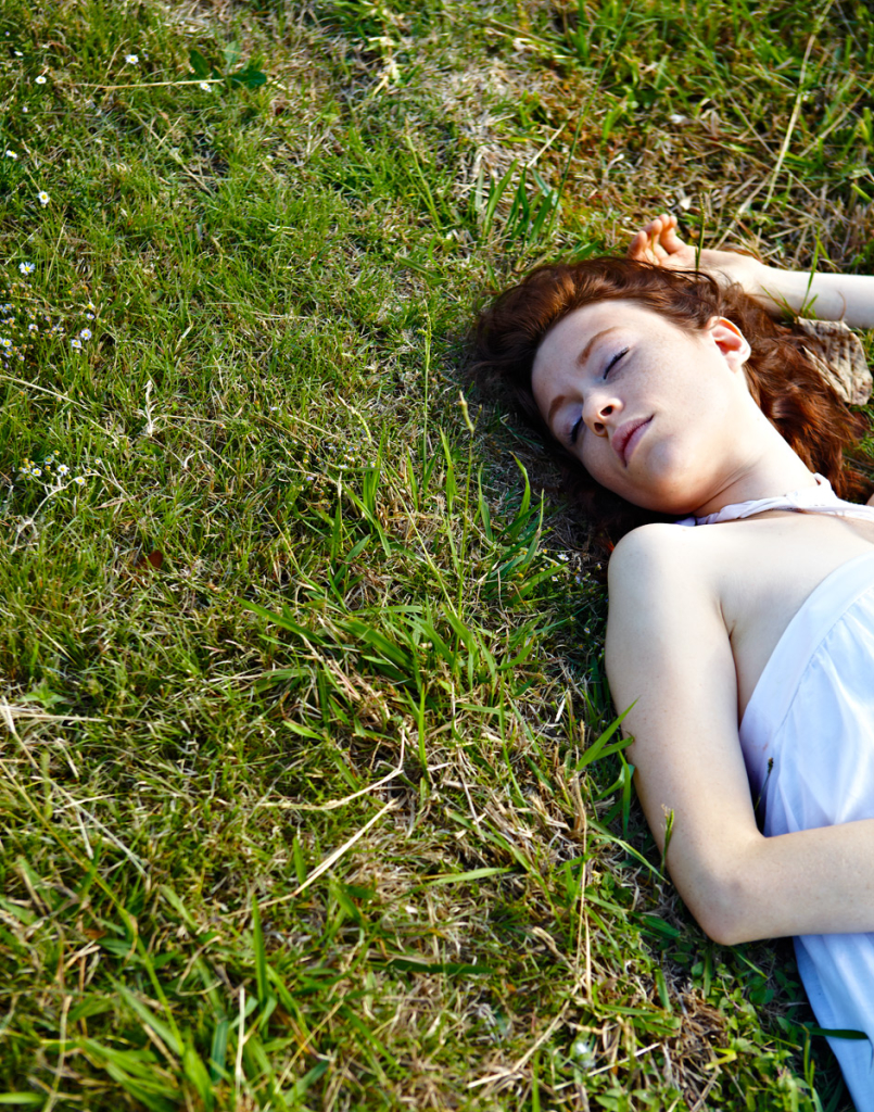 Lady lays in grass with eyes closed